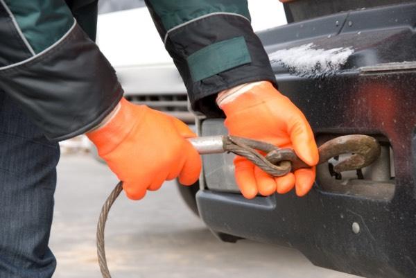 Автослесарь крепит галстук для буксировки автомобиля (фото)